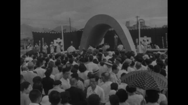 arched memorial structure the hiroshima peace memorial being unveiled / crowd gathered in front of memorial structure / cu crying woman in crowd... - pazifikkrieg stock-videos und b-roll-filmmaterial