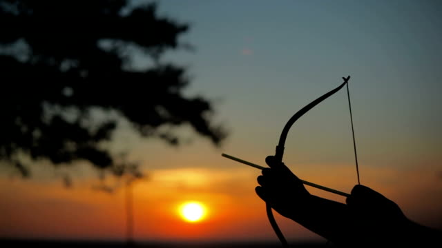 archery aiming arrow at sun during sunset - archery bow stock videos and b-roll footage