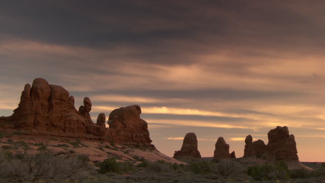 arches national park spires and red rock formations at sunset with wispy clouds - arches national park stock videos and b-roll footage