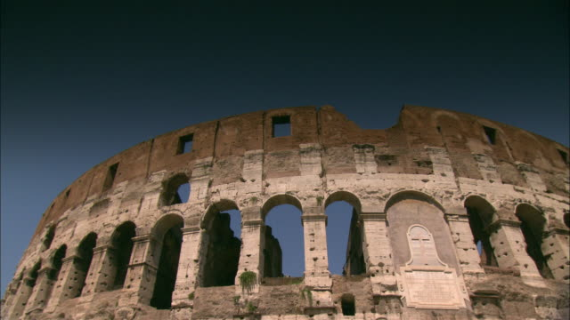 arches ring the stone ruins of rome's colosseum. - bogen architektonisches detail stock-videos und b-roll-filmmaterial