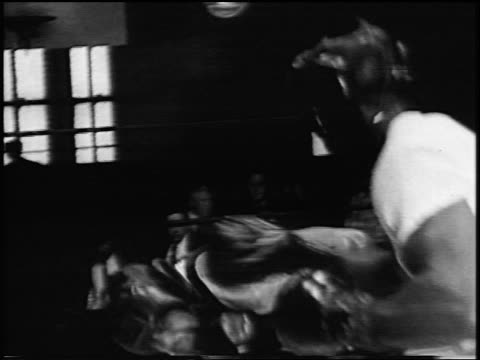 Archie Moore boxing other man in training in gym / newsreel
