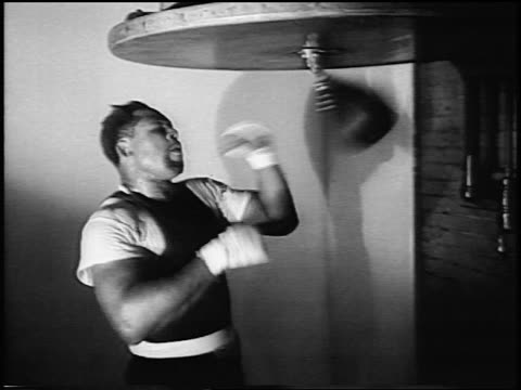 Archie Moore punching speed bag in training in gym / newsreel