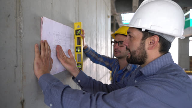 architect and an engineer talking about a blueprint leaning against the wall and pointing at it - strumento di misura video stock e b–roll