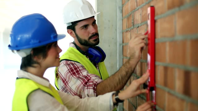 Architect and builder marking a wall at the construction site
