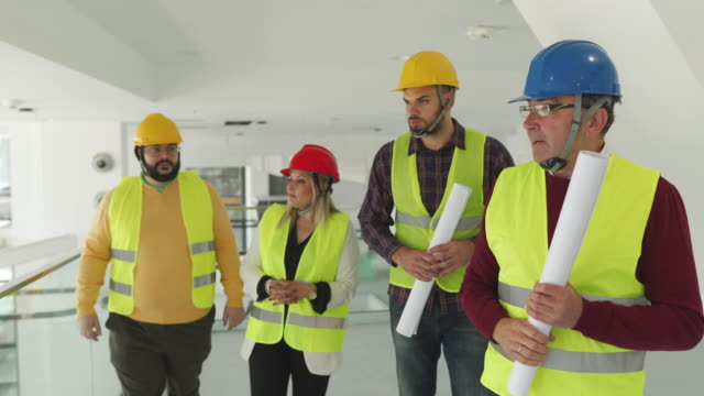 architect and construction workers walking through building and talking about work progress - white caucasian stock videos & royalty-free footage