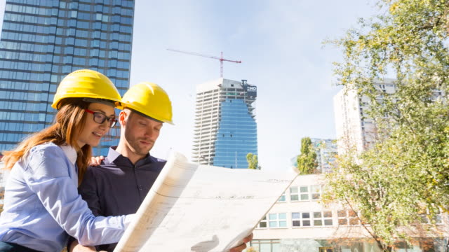ms architect and contractor discussing building plans in front of high rise construction - baustelle stock-videos und b-roll-filmmaterial