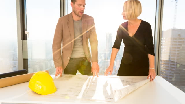 MS architect and contractor discussing building plans in office