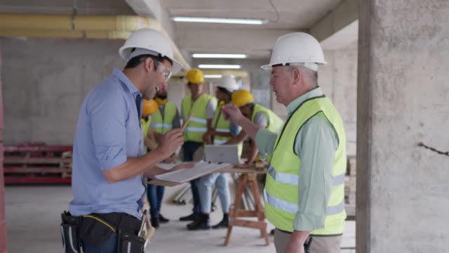 短い会話の後、建設現場で握手を交わす建築家と請負業者 - 土木技師点の映像素材/bロール