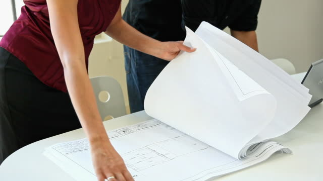 architect and designer reviewing blueprints with laptop - employee engagement stock videos & royalty-free footage