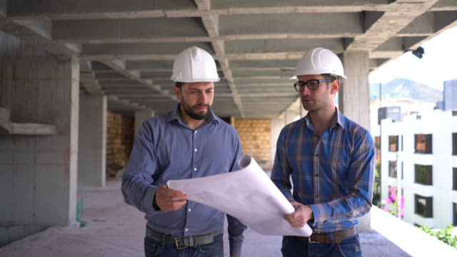 architect and engineer looking at the construction site and a blueprint both looking very satisfied and handshaking - architect stock videos & royalty-free footage