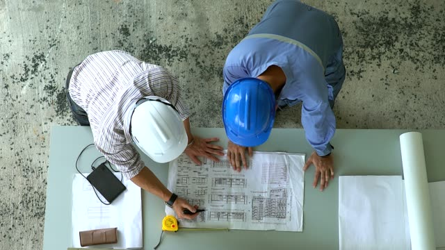 architect and engineer meeting planning for a new project with construction equipment on the table. - contractor stock videos and b-roll footage