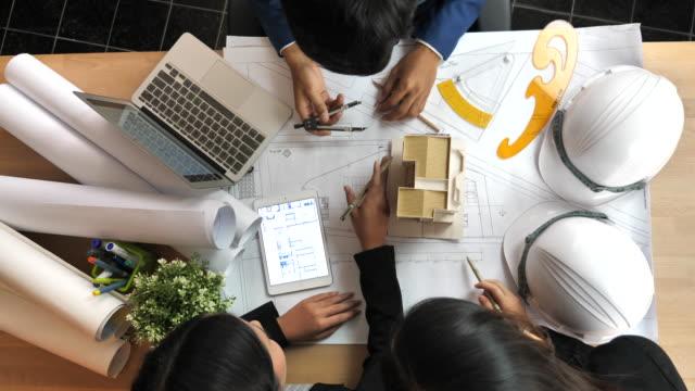 建築家および建物の平面図上の議論を持つエンジニア チーム - 工業技術点の映像素材/bロール