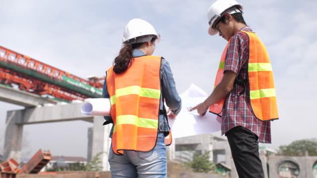 Architekt und Ingenieur mit Blaupausen sprechen auf Baustelle