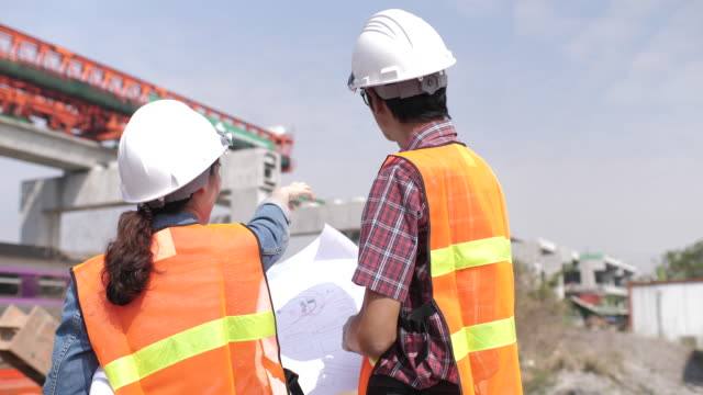 Architect and engineer with blueprints talking at construction site