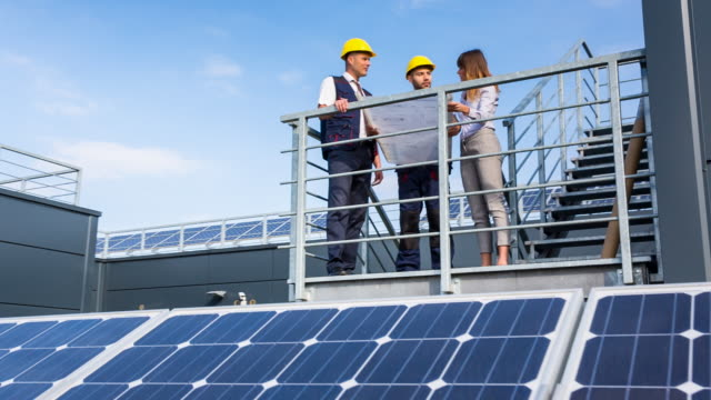 WS architect and engineers discussing solar panels on rooftop