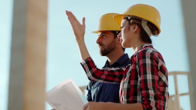 vidéos et rushes de architecte et foreman examinant les travaux en cours sur le chantier - chantier de construction