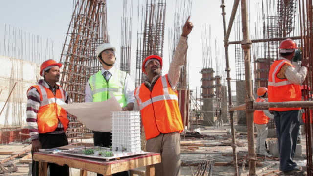 vidéos et rushes de architect discussing with his team, delhi, india - chantier de construction