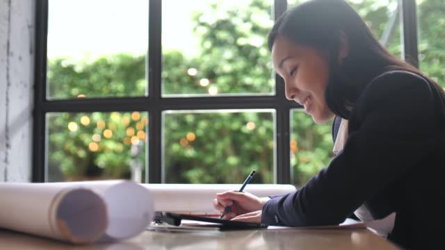 arkitekten utarbeta ritningar, med hjälp av linjal och penna - endast en medelålders kvinna bildbanksvideor och videomaterial från bakom kulisserna