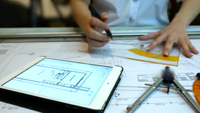 architect drawing and comparing a blue print structure with digital tablet, 4k(uhd) - drawing activity stock videos & royalty-free footage