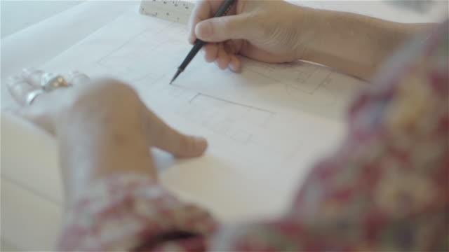 architect drawing at drafting table close up. - 製図板点の映像素材/bロール