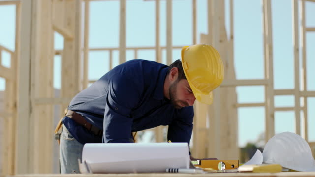 Architect drawing blueprints for house at construction site