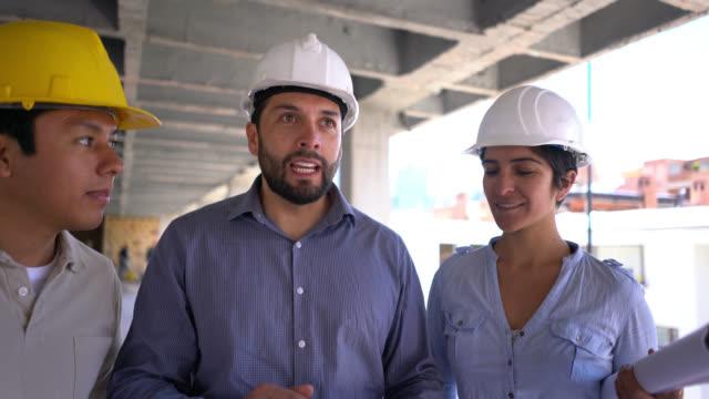 stockvideo's en b-roll-footage met architect, ingenieur en bouw werknemer bespreking van het project op de bouwplaats allen op zoek zeer gelukkig en lachende - positieve emotie