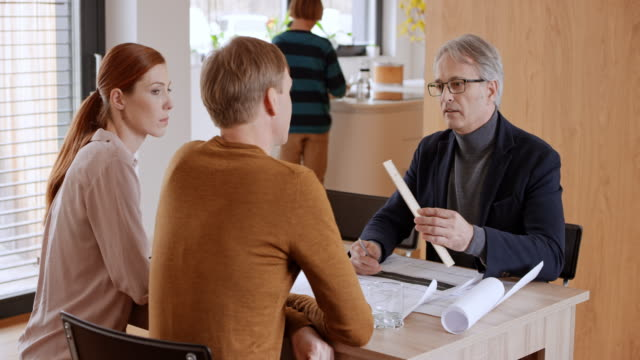 Architect explaining plan details to couple in their dining room