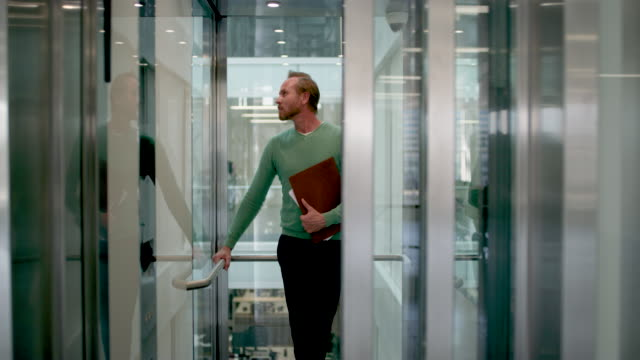 ms of architect getting into elevator in modern office - eintreten stock-videos und b-roll-filmmaterial