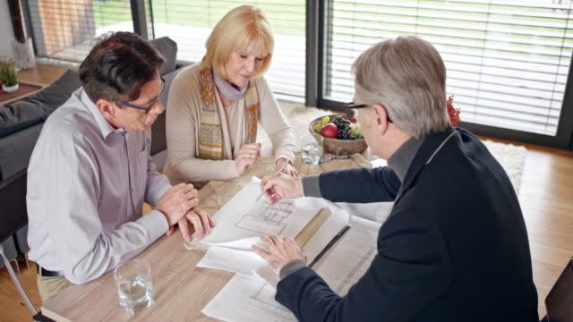 Architekt mit einem Treffen mit einem älteren Paar in ihrem Haus