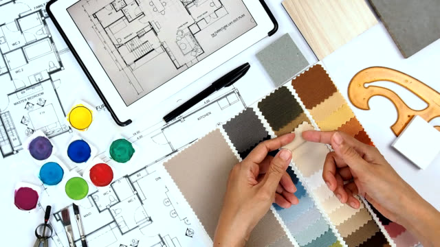 Architect & interior designer working at worktable withfabric swatch, tablet, blue print