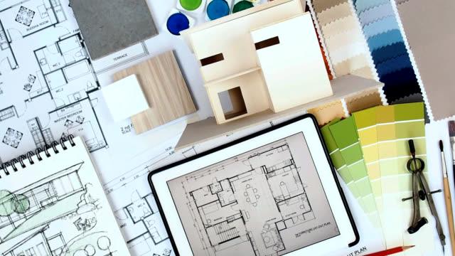 vídeos y material grabado en eventos de stock de mesa de trabajo diseñador arquitecto & interior con casa modelo, tableta, impresión azul - table top view