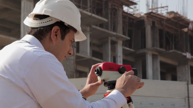 Architect lookiing through theodolite instrument in the construction site, Delhi, India