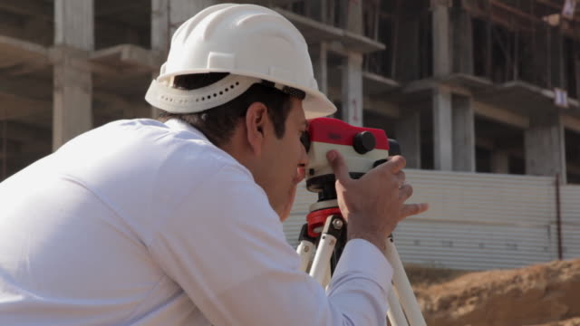 architect lookiing through theodolite instrument in the construction site, delhi, india - ヘルメット点の映像素材/bロール