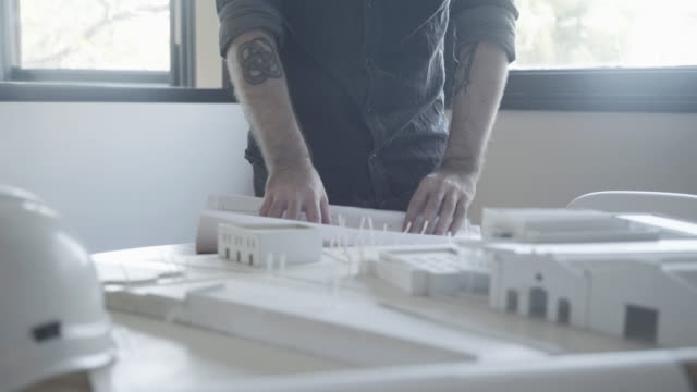 architect looking at blueprint and architectural model - hochgekrempelte ärmel stock-videos und b-roll-filmmaterial