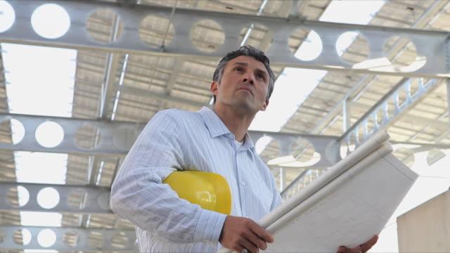 vídeos de stock, filmes e b-roll de ms la tu architect looking at blueprints under solar panel arrary/ richmond, virginia, usa - diagrama