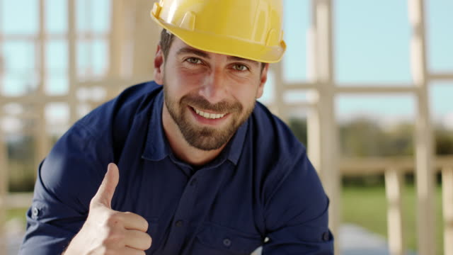 architect looking at camera and showing thumbs up at construction site - helmet stock videos & royalty-free footage