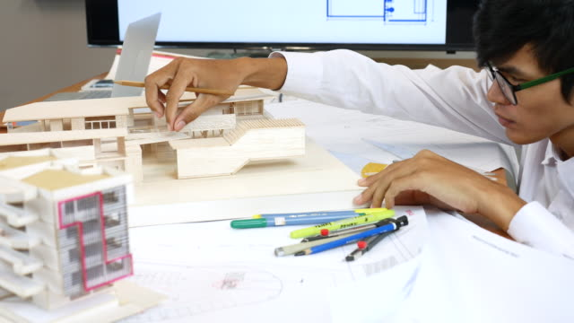 Architect looking at Model with sketch of construction in office