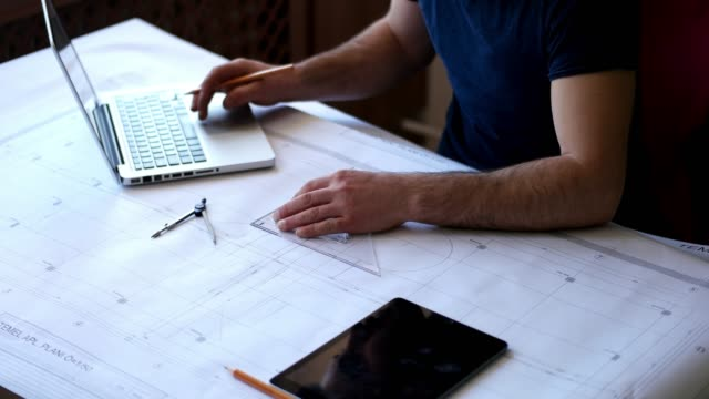 Architect making floor plans using computer and graph tools