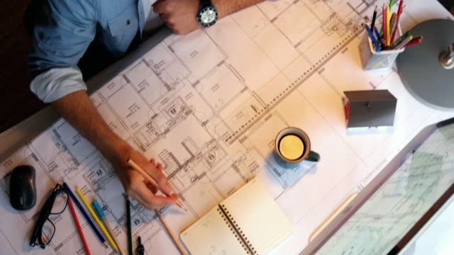 architect man holding pencil working with laptop and blueprints for architectural plan, engineer sketching a construction project concept. - sketch stock videos & royalty-free footage