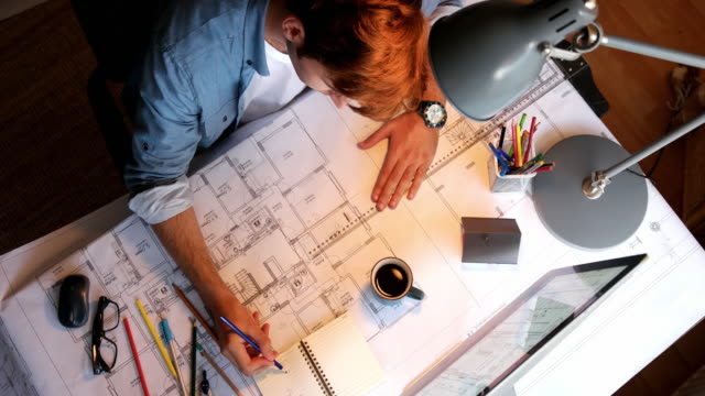 architect man holding pencil working with laptop and blueprints for architectural plan, engineer sketching a construction project concept. - architect stock videos and b-roll footage