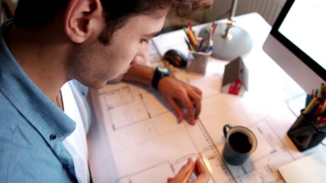 vidéos et rushes de homme tenant le crayon de travail avec ordinateur portable et des plans pour le plan architectural, ingénieur en esquissant une idée de projet de construction de l'architecte. - agence de design