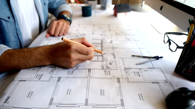vídeos de stock e filmes b-roll de architect man holding pencil working with laptop and blueprints for architectural plan, engineer sketching a construction project concept. - cópia heliográfica