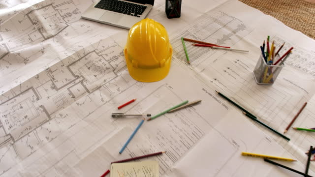 architect man holding pencil working with laptop and blueprints for architectural plan, engineer sketching a construction project concept. - tavolo video stock e b–roll