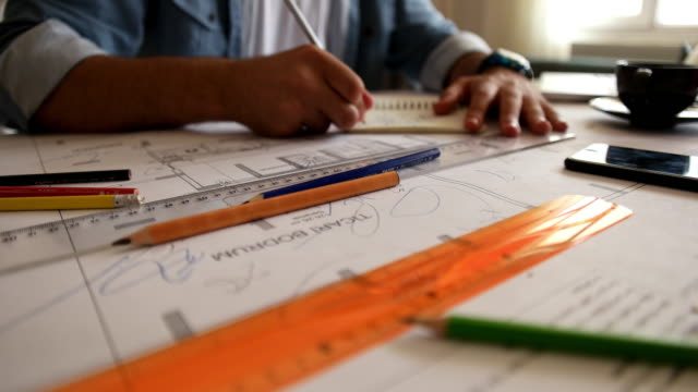 architect man holding pencil working with laptop and blueprints for architectural plan, engineer sketching a construction project concept. - architect stock videos & royalty-free footage