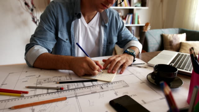 architect man holding pencil working with laptop and blueprints for architectural plan, engineer sketching a construction project concept. - architetto video stock e b–roll