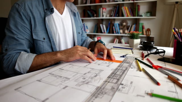 architect man holding pencil working with laptop and blueprints for architectural plan, engineer sketching a construction project concept. - disegno video stock e b–roll