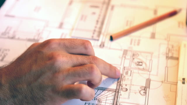 architect man holding pencil working with laptop and blueprints for architectural plan, engineer sketching a construction project concept. - blueprint stock videos & royalty-free footage