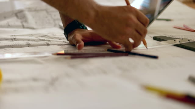 architect man holding pencil working with laptop and blueprints for architectural plan, engineer sketching a construction project concept. - simplicity stock videos and b-roll footage