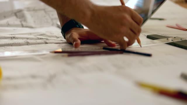 vídeos de stock, filmes e b-roll de o arquiteto homem segurando o lápis, trabalhando com o laptop e especificações técnicas para o plano arquitectónico, engenheiro esboçar um conceito de projeto de construção. - compasso