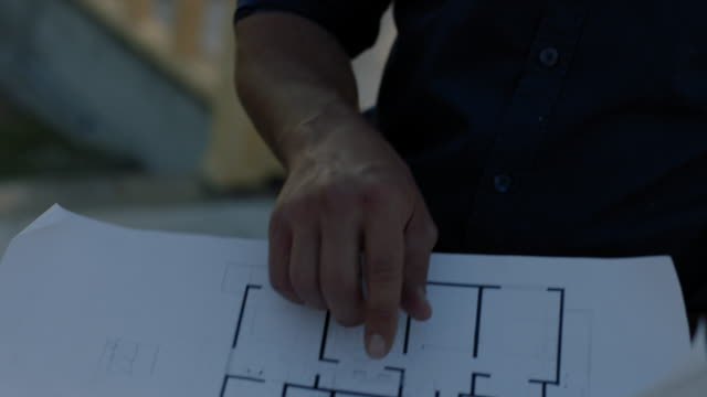 Architect pointing at blueprints